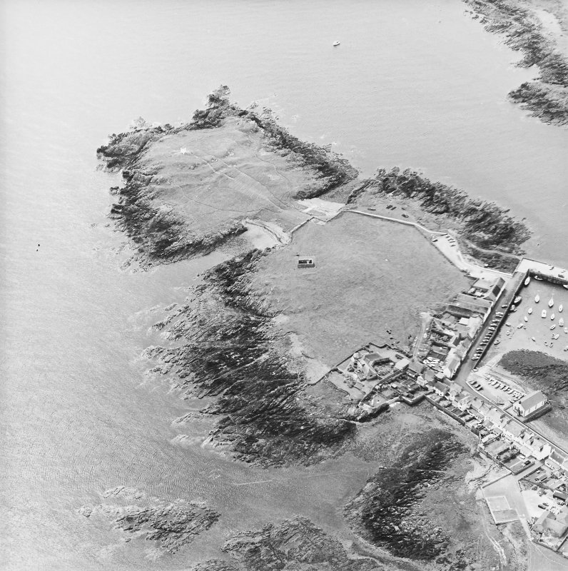 Oblique aerial view centred on the remains of the chapel with the remains of the promontory fort and the village adjacent, taken from the N.