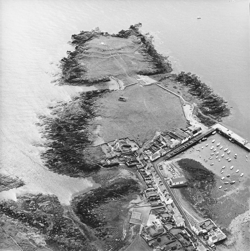 Oblique aerial view centred on the remains of the chapel with the remains of the promontory fort and the village adjacent, taken from the NNW.
