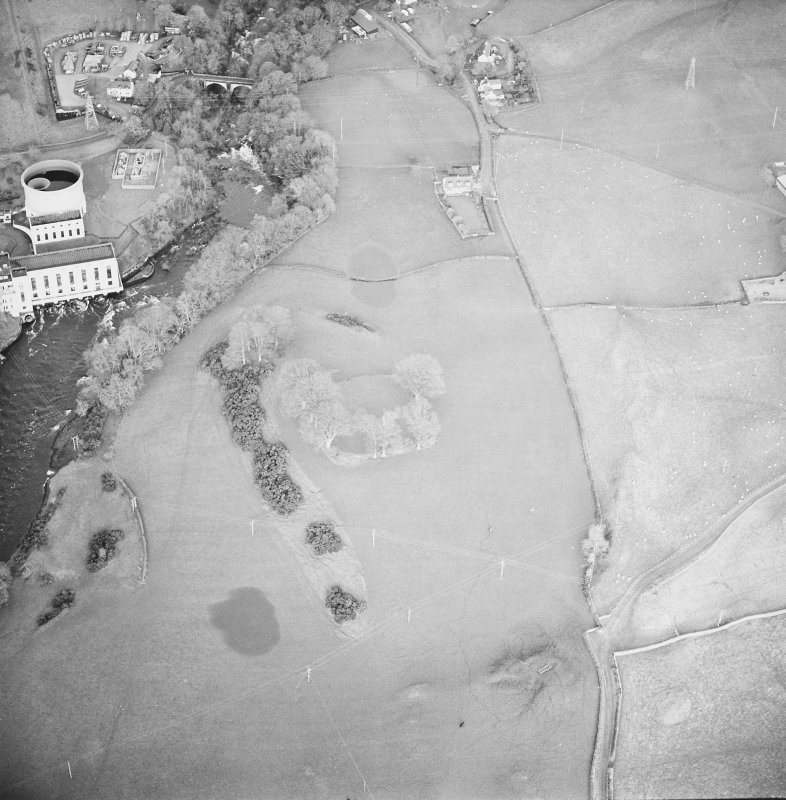 Oblique aerial view centred on the remains of the fort with power station and road bridge adjacent, taken from the SW.