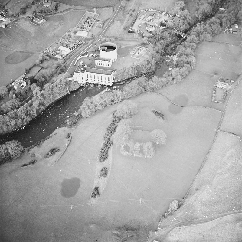 Oblique aerial view centred on the remains of the fort with power station and road bridge adjacent, taken from the SSW.