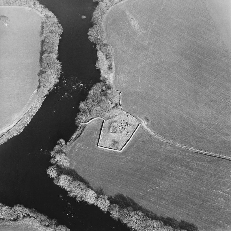 Oblique aerial view centred on the remains of the church and burial ground with the remains of a motte in trees adjacent, taken from the W.