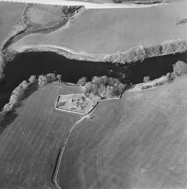 Oblique aerial view centred on the remains of the church and burial ground with the remains of a motte in trees adjacent, taken from the S.