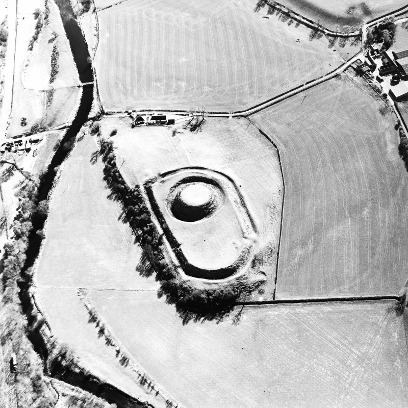 Oblique aerial view centred on the remains of the motte-and-bailey castle, taken from the NNW.