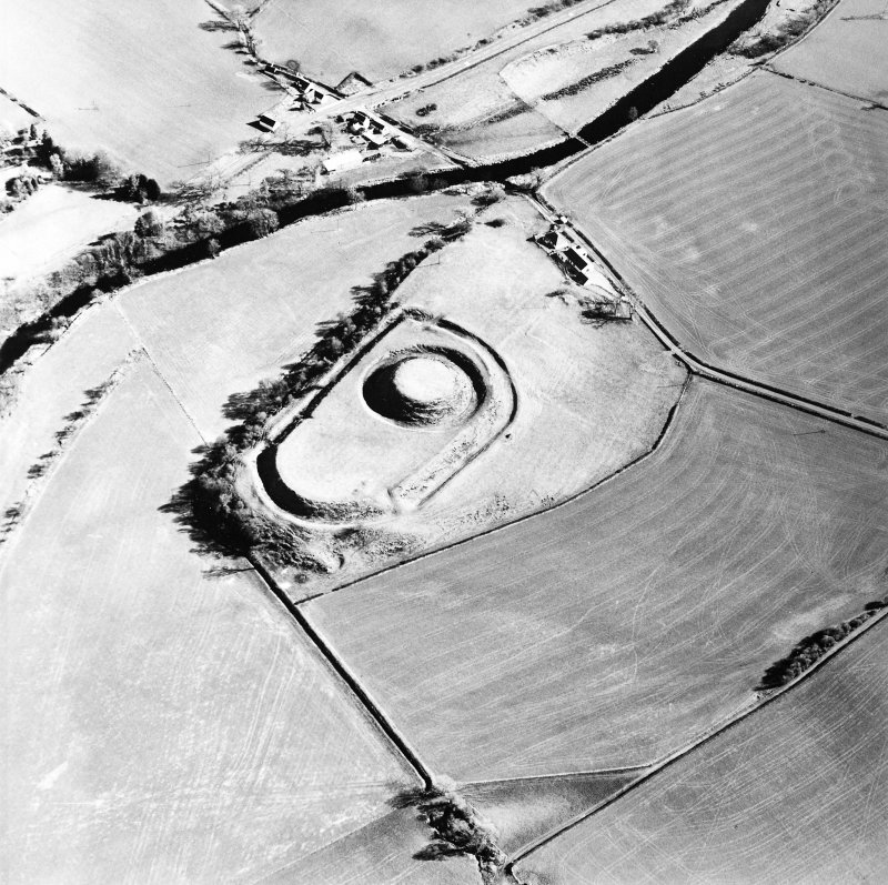 Oblique aerial view centred on the remains of the motte-and-bailey castle, taken from the WNW.