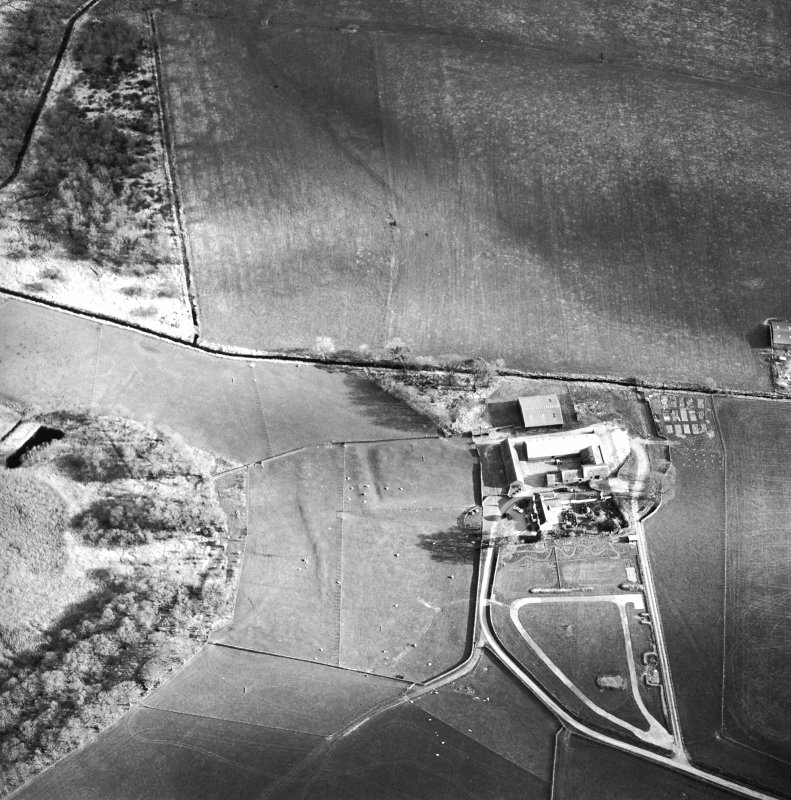 Oblique aerial view centred on the remains of the moat with farmsteading adjacent, taken from the NNW.