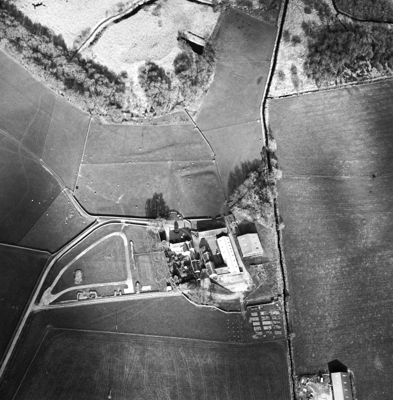 Oblique aerial view centred on the remains of the moat with farmsteading adjacent, taken from the WSW.