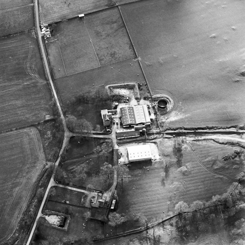 Oblique aerial view centred on the tower house with rig adjacent, taken from the ENE.