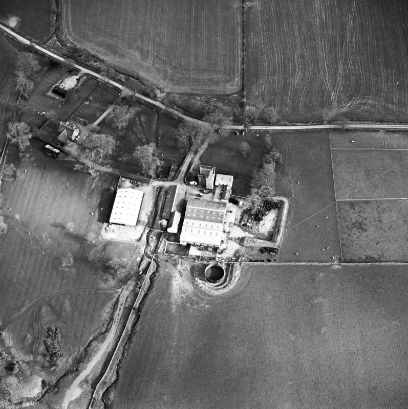 Oblique aerial view centred on the tower house with rig adjacent, taken from the NW.