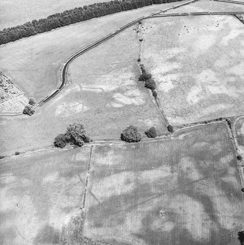 Holywood Abbey, oblique aerial view, taken from the SW, centred on the cropmarks to the SE of the Abbey, and showing a rectilinear enclosure and linear cropmarks (Dalawoodie) in the bottom half of the photograph.
