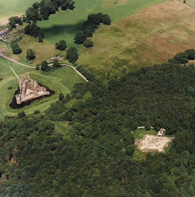 Oblique aerial view centred on the remains of the castle and excavation of the old castle, taken from the S.