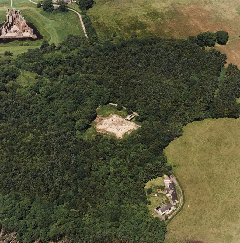 Oblique aerial view centred on the excavation of the old castle with castle adjacent, taken from the SSE.