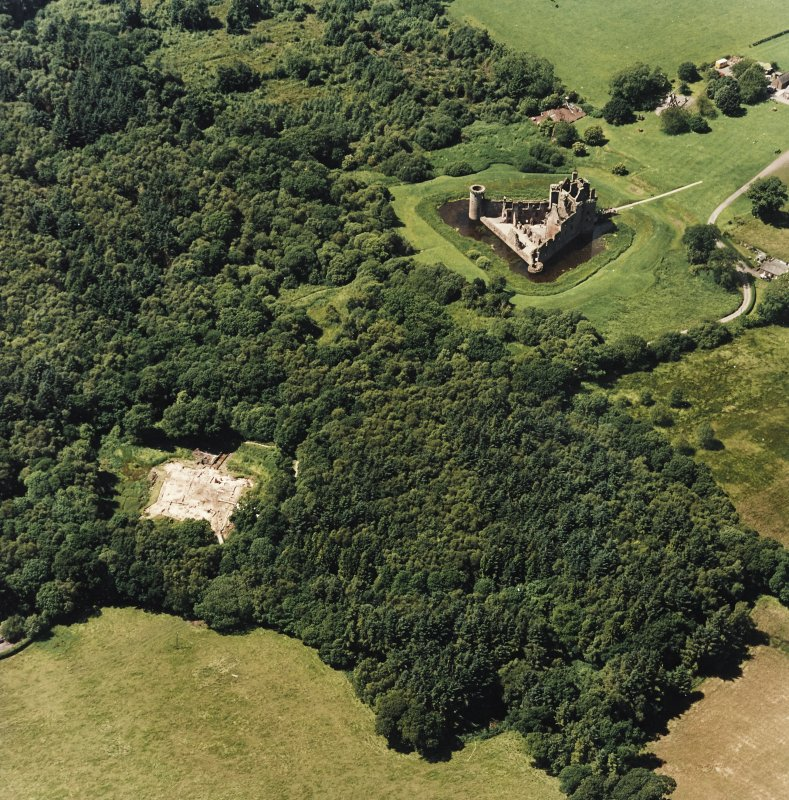 Oblique aerial view centred on the remains of the castle and excavation of the old castle, taken from the E.
