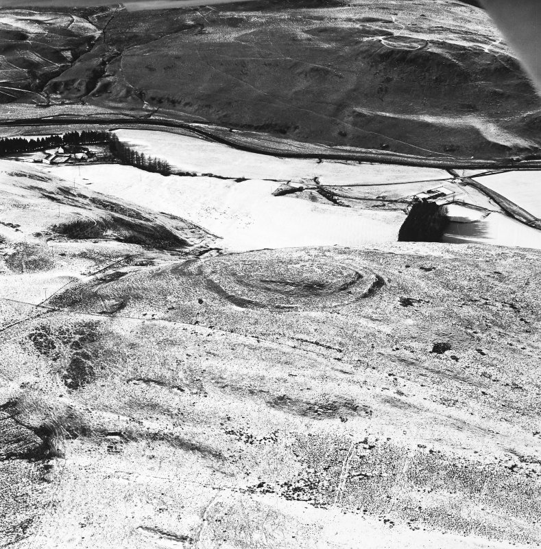 Rangecastle Hill, oblique aerial view, taken from the E, centred on the remains of a fort and round house, with another fort to the top of the photograph.