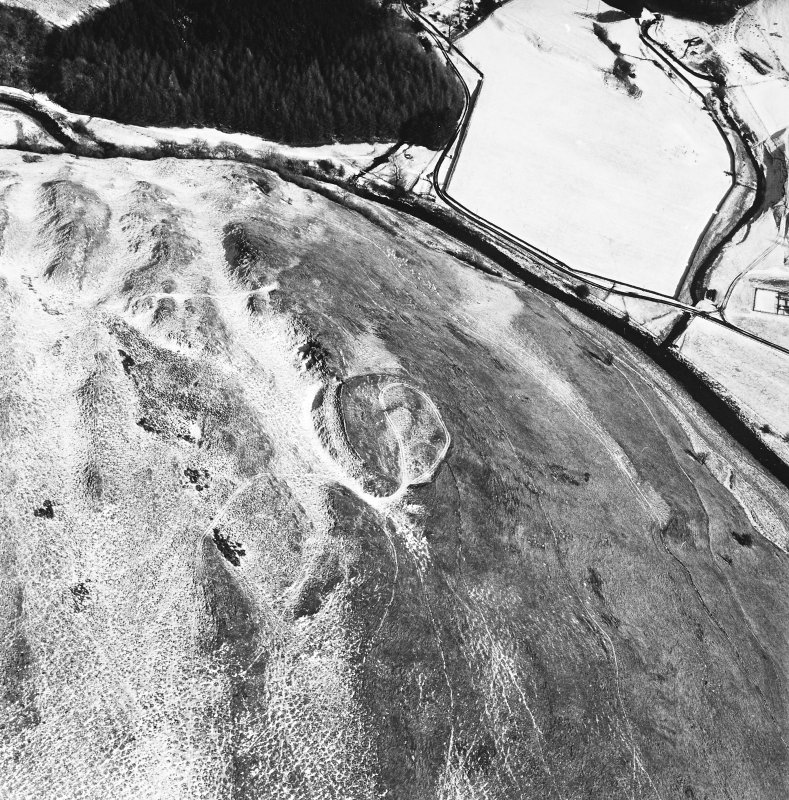 Carthur Hill, oblique aerial view, taken from the SW, centred on a fort and cultivation remains.