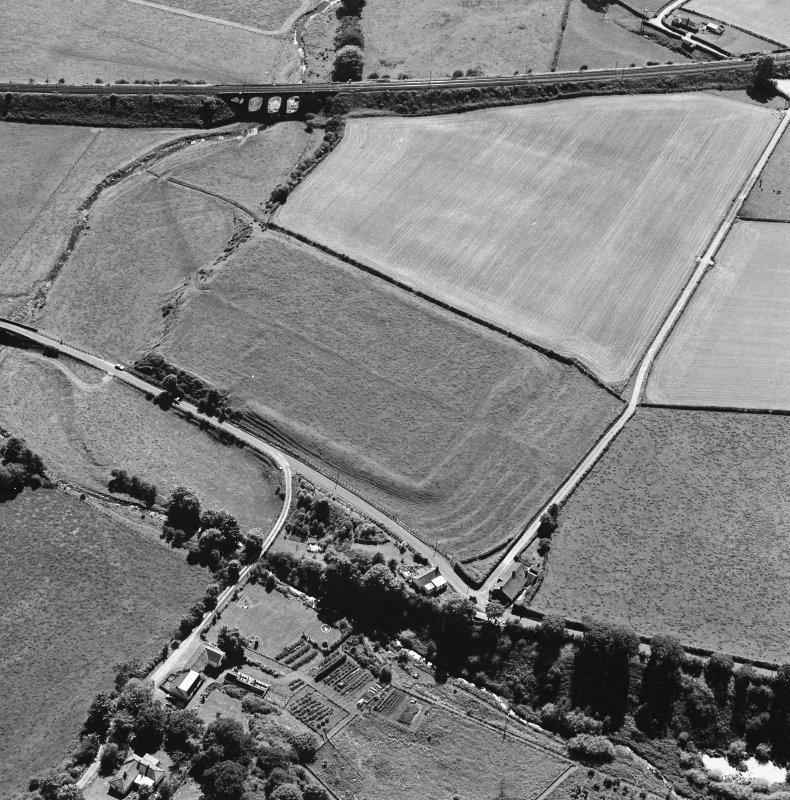 Oblique aerial view of Birrens, taken from the NE, centred on a Roman Fort.  A watermill, situated to the E of the fort is visible in the bottom left-hand corner of the photograph.
