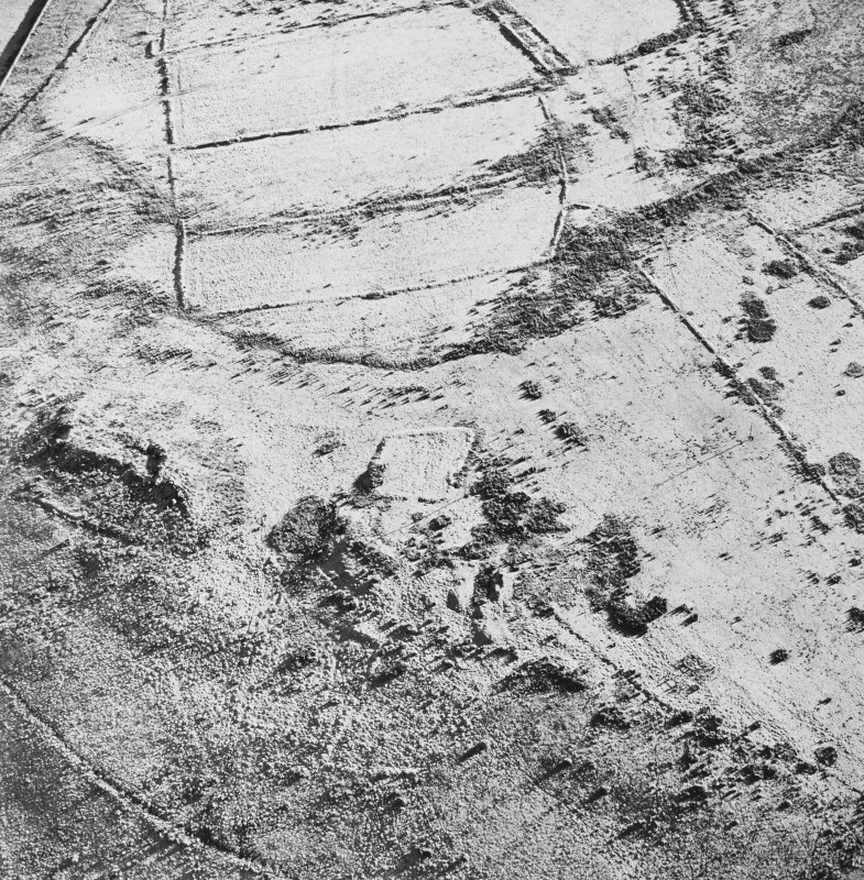 Oblique aerial view of Toft Knowes centred on the remains of a farmstead and quarries surrounded by a field-system, rig and pens, taken from the WNW.