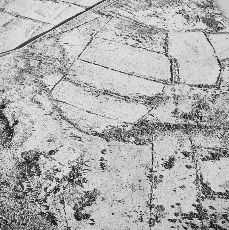 Oblique aerial view of Toft Knowes centred on the remains of a farmstead and quarries surrounded by a field-system, rig and pens with a settlement in the upper right corner of the photograph, taken from the W.