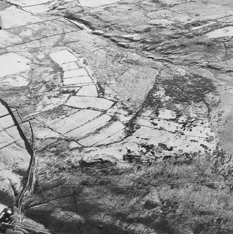 Oblique aerial view of Toft Knowes centred on the remains of a field-system, rig and pens with a farmstead and quarries and a settlement adjacent, taken from the NNW.