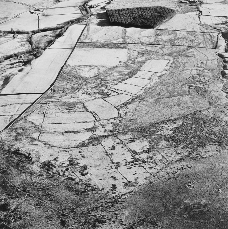 Oblique aerial view of Toft Knowes centred on the remains of a field-system, rig and pens with a farmstead and quarries and a settlement adjacent, taken from the WNW.
