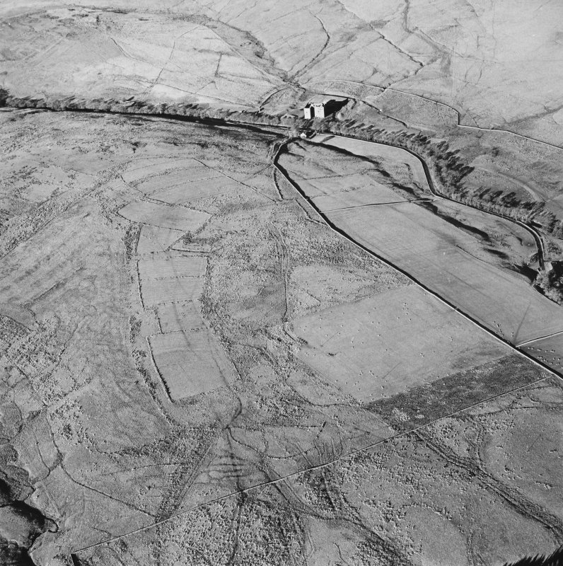 Oblique aerial view of Toft Knowes centred on the remains of a field-system, rig and pens with a farmstead and quarries and a settlement adjacent and a castle in the background, taken from the SE.