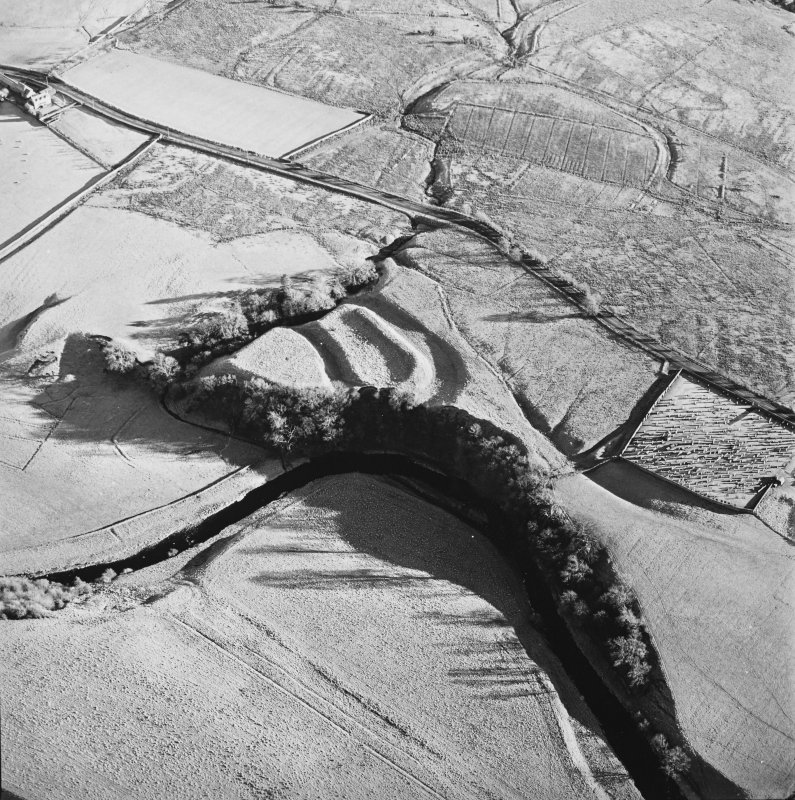 Oblique aerial view of Liddel Castle centred on the remains of an earthwork fortification with a burial ground and remains of a church adjacent, from NW.