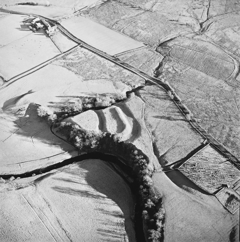 Oblique aerial view of Liddel Castle centred on the remains of an earthwork fortification with a burial ground and remains of a church adjacent, from WNW.