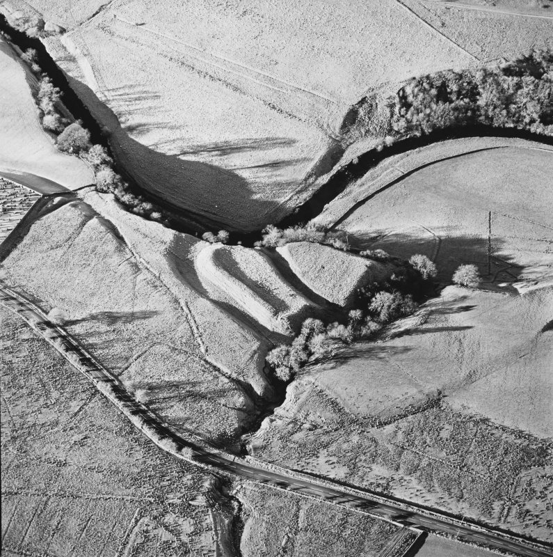 Oblique aerial view of Liddel Castle centred on the remains of an earthwork fortification, taken from the ESE.