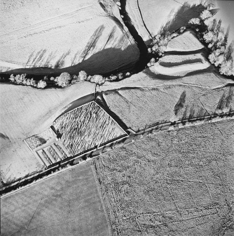 Oblique aerial view of Castleton centred on a burial ground and remains of a church with the remains of an earthwork fortification adjacent, from S.