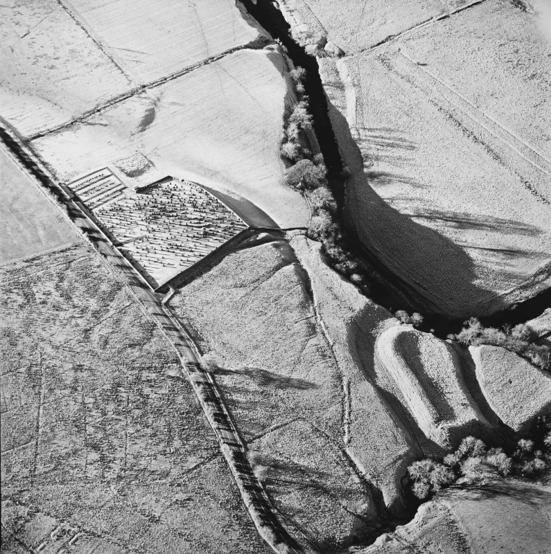 Oblique aerial view of Castleton centred on a burial ground and remains of a church with the remains of an earthwork fortification adjacent, from E.