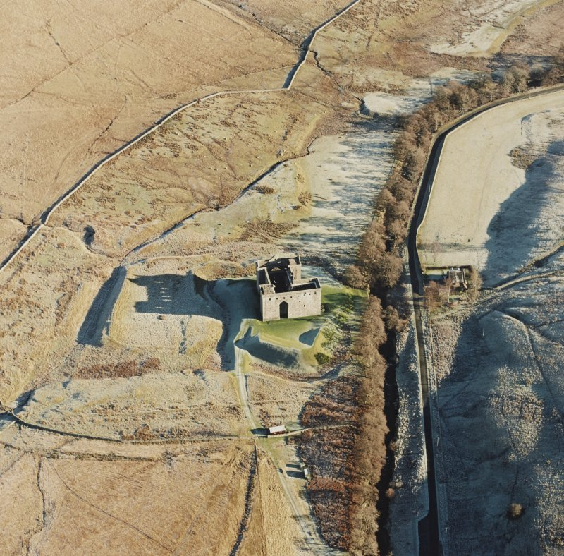 Oblique aerial view of Hermitage Castle centred on the remains of a castle and earthwork castle, taken from the W.