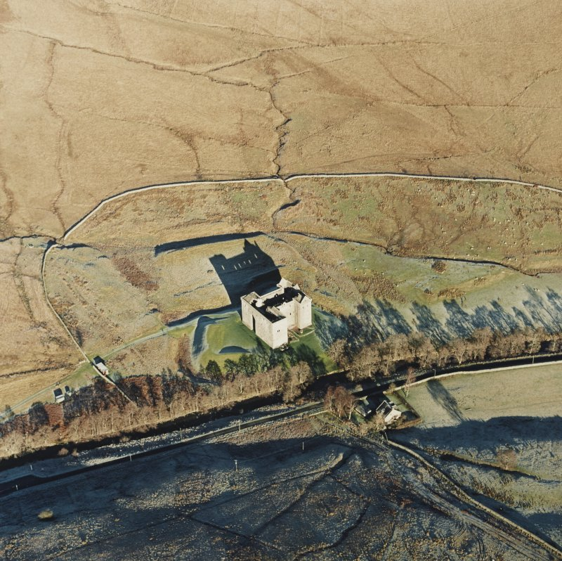 Oblique aerial view of Hermitage Castle centred on the remains of a castle and earthwork castle, taken from the SSW.