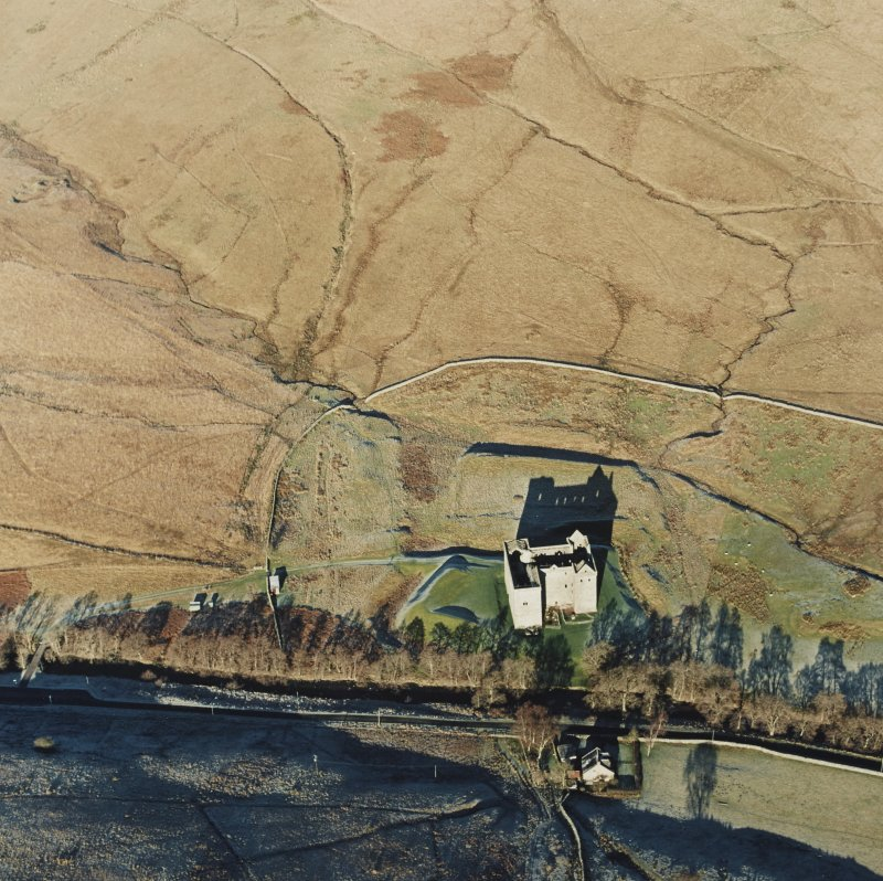 Oblique aerial view of Hermitage Castle centred on the remains of a castle and earthwork castle, taken from the S.