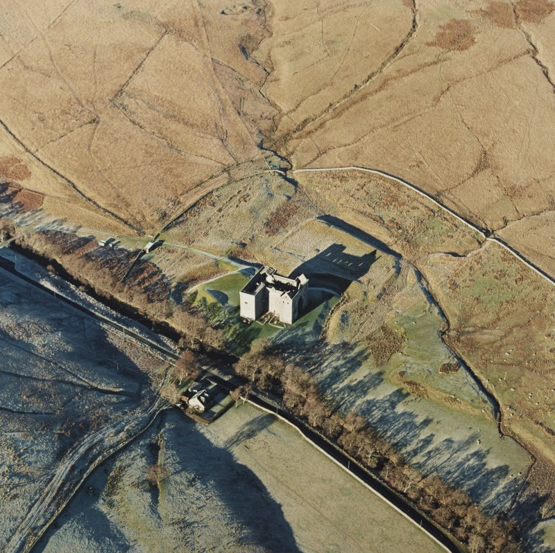 Oblique aerial view of Hermitage Castle centred on the remains of a castle and earthwork castle, taken from the SE.