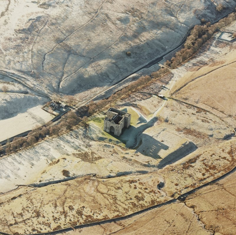 Oblique aerial view of Hermitage Castle centred on the remains of a castle and earthwork castle with the remains of a chapel, moated site and boundary dyke adjacent, taken from the NE.