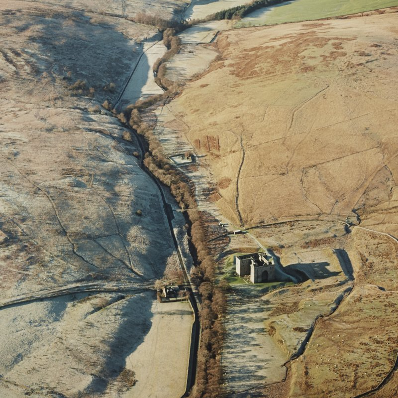 Oblique aerial view of Hermitage Castle centred on the remains of a castle and earthwork castle with the remains of a chapel, moated site and boundary dyke adjacent, taken from the E.