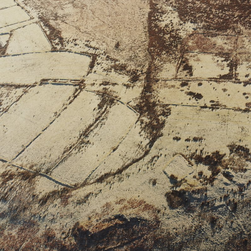 Oblique aerial view of Toft Knowes centred on the remains of a farmstead and quarries with the remains of a field-system, rig and pens adjacent, taken from the N.