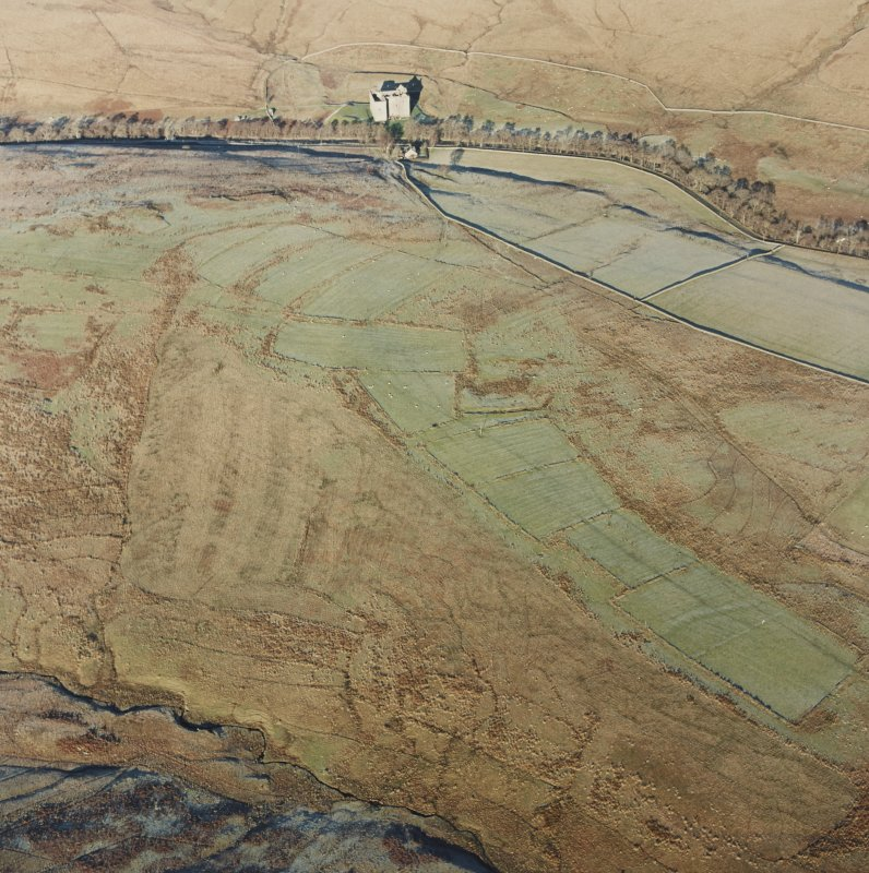 Oblique aerial view of Toft Knowes centred on the remains of a field-system, rig and pens with the remains of a farmstead, quarries and settlement adjacent and Hermitage Castle in the background, taken from the S.