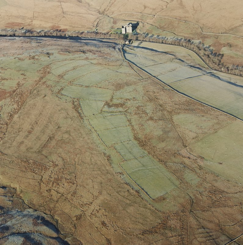 Oblique aerial view of Toft Knowes centred on the remains of a field-system, rig and pens with the remains of a farmstead, quarries and settlement adjacent and Hermitage Castle in the background, take ...