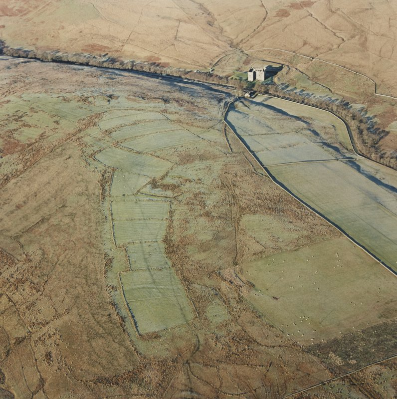Oblique aerial view of Toft Knowes centred on the remains of a field-system, rig and pens with the remains of a farmstead, quarries and settlement adjacent and Hermitage Castle in the background, taken from the SSE.