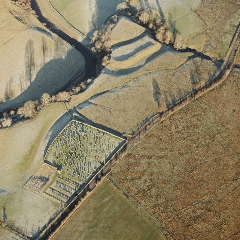 Oblique aerial view of Castleton centred on a burial-ground and remains of an earthwork fortification, from SW.