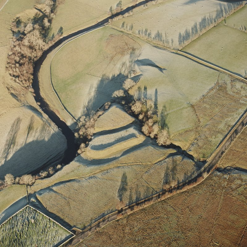 Oblique aerial view of Liddel Castle centred on the remains of an earthwork fortification, taken from the SSW.