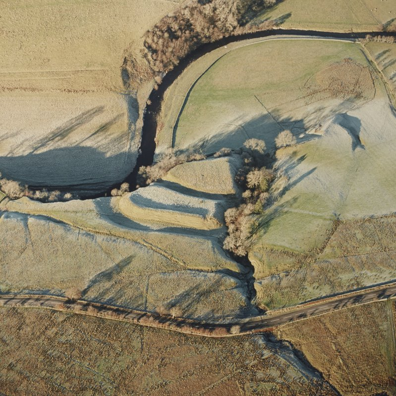 Oblique aerial view of Liddel Castle centred on the remains of an earthwork fortification, taken from the SSE.