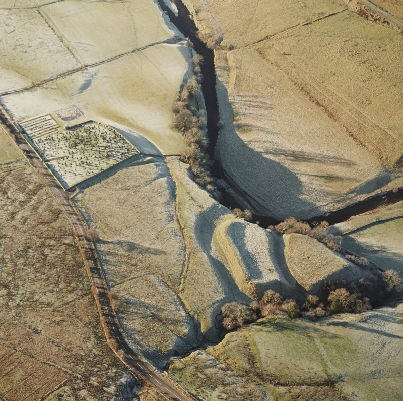 Oblique aerial view of Liddel Castle centred on the remains of an earthwork fortification and burial-ground, from E.