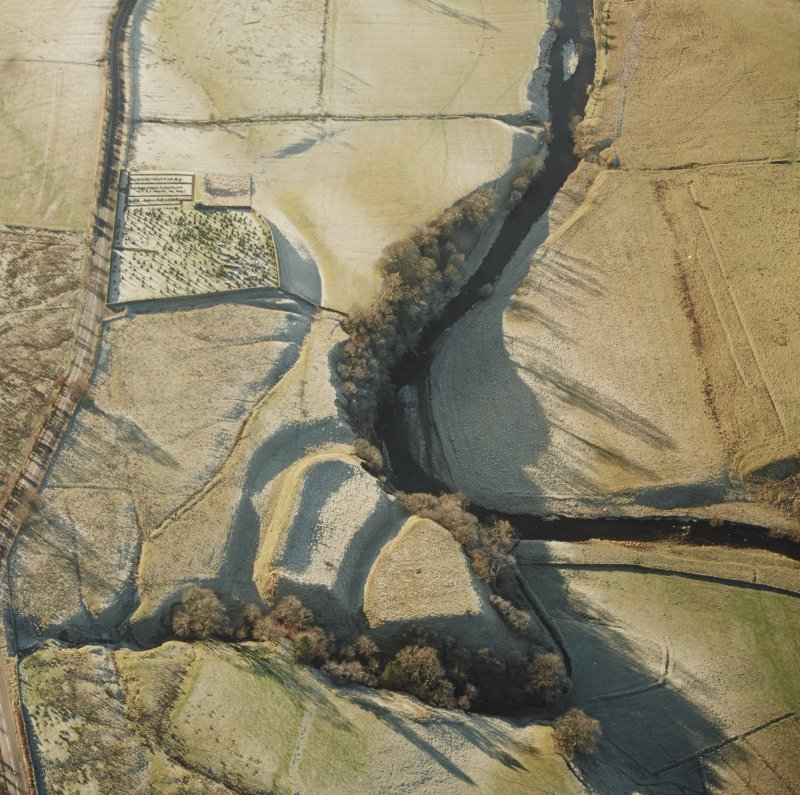 Oblique aerial view of Liddel Castle centred on the remains of an earthwork fortification and burial-ground, from NE.
