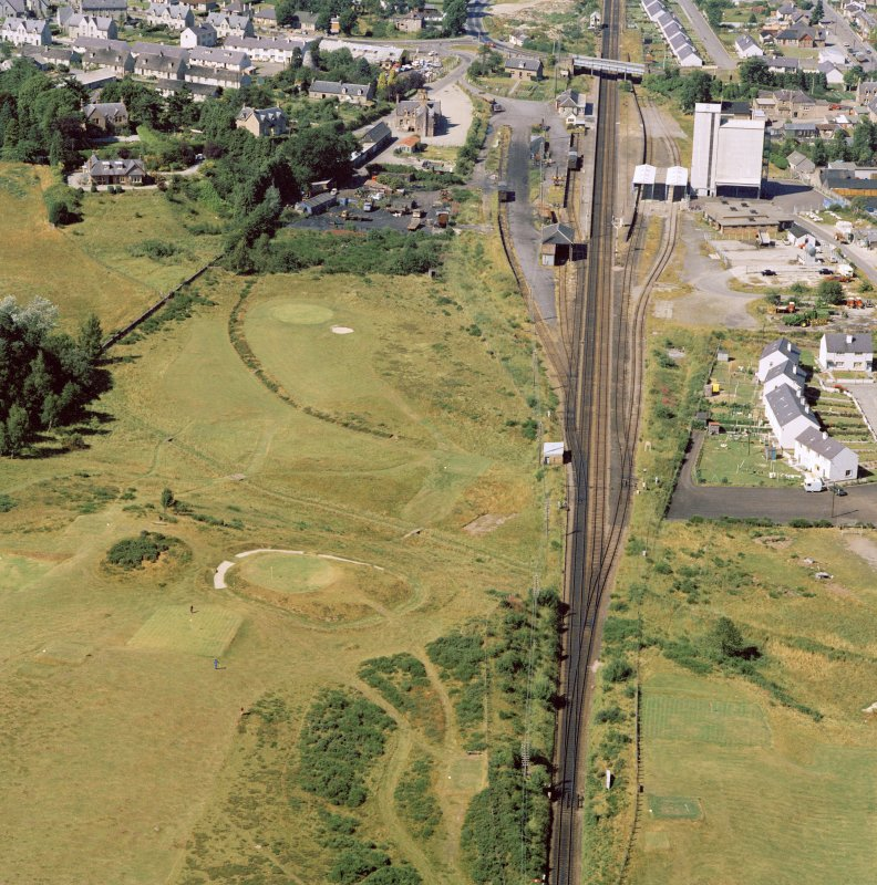 Oblique aerial view of the remains of Muir of Ord henge, Castle Hill.