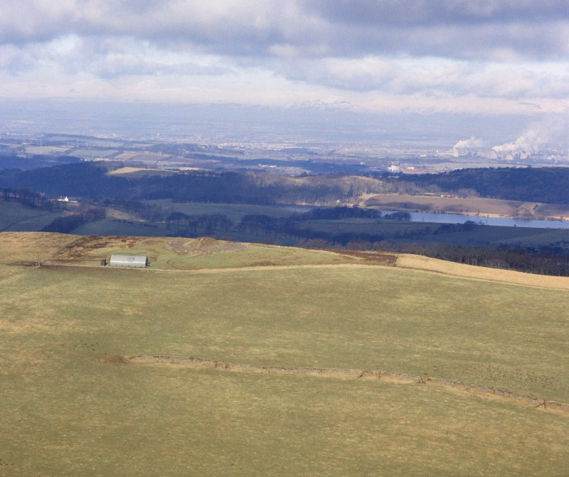 Oblique aerial view centred on the remains of Cairnpapple henge and cairn.