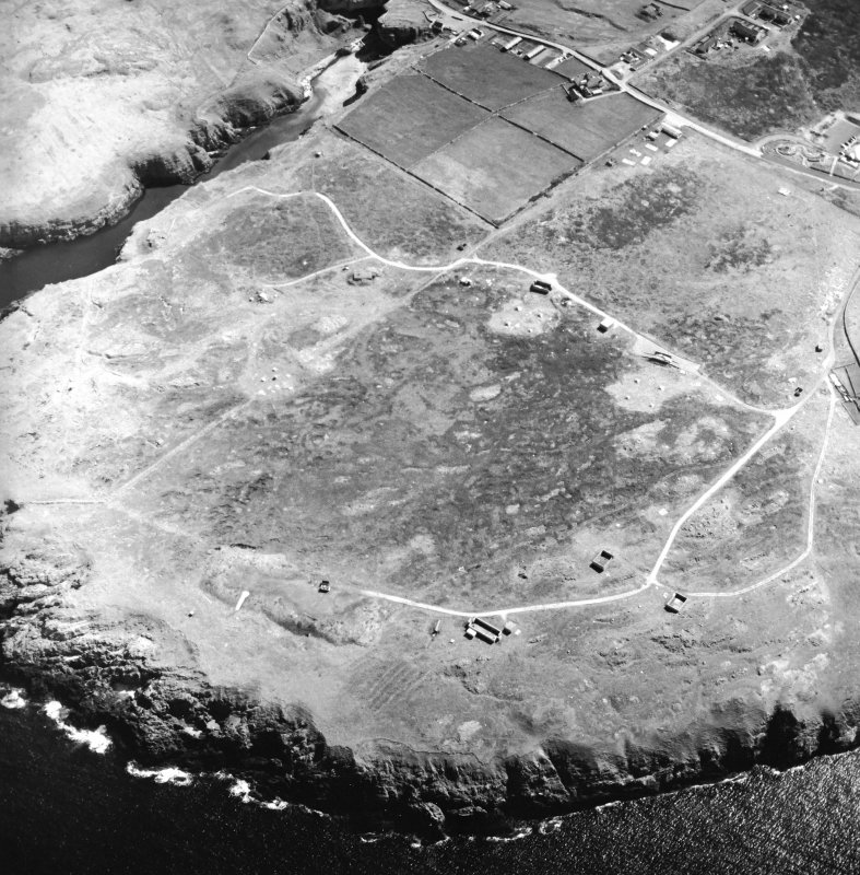 Oblique aerial view centred on the remains of the radar station with caves and crofting township adjacent, taken from the NNW.