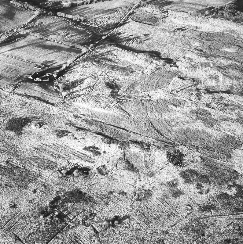 Machrie Moor and Moss Farm, oblique aerial view, with the stone circles in the top half of the photograph and a hut-circle and possible hut-circle in the bottom half.