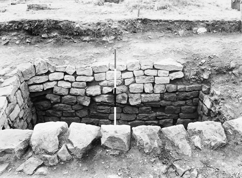 Rough Castle Roman Fort Excavation photograph: stone-lined pit at N end of Via Principalis, as excavated 1961.