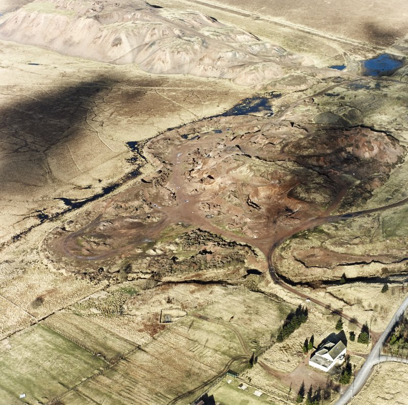 Tarbrax shale-oil works, oblique aerial view, taken from the S, showing the shale-oil mine's large spoil heaps across the centre and top half of the photograph, and the edge of Tarbrax village in the botom right-hand corner.